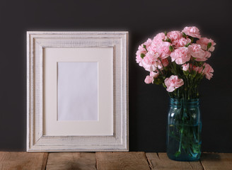 A horizontal presentation of a rustic white wood frame and a teal glass vase with pink carnations.  A black background provides the perfect mock up presentation for your business concept.