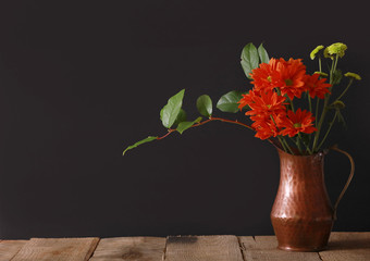 Bright red flowers with green leaves in a copper pitcher vase on a wood table with a striking black background.
