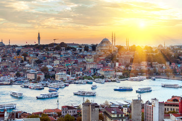 Tourist boat sails on the Golden Horn in Istanbul at sunset, Turkey.