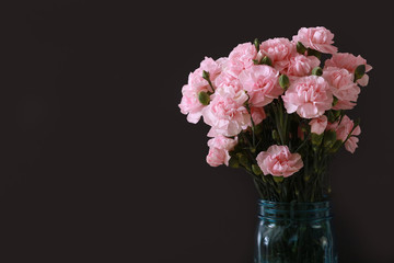 Pink miniature carnations in a teal glass vase and a black background with text copy space available on the left side.