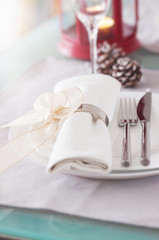 Elegant decorated Christmas table setting with modern cutlery, napkin, bow and christmas decorations. Christmas menu concept, closeup