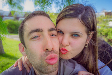 Couple having fun making duckface and taking selfie picture in t