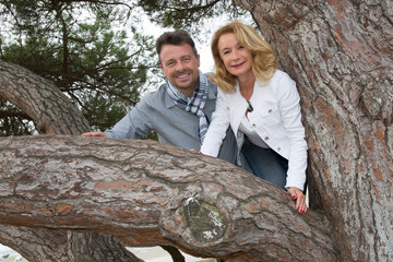 Lovely couple in park leaning against tree