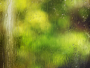 Wet window abstract background photograph with blurred trees, rain drops,  and streams of water.