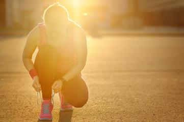 Woman runner tying laces before training. Marathon.