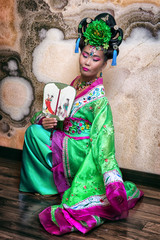 attractive asian woman wearing chinese traditional dress with fan, sitting on her knee