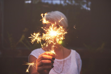 Woman hand holding sparkler outdoors