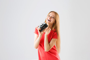 portrait of a smiling attractive young woman taking photos using old camera.
