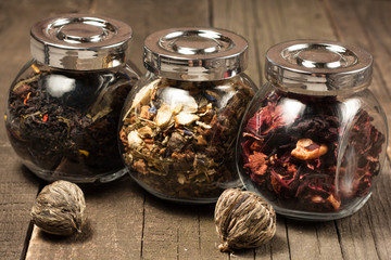 Dry tea in glass jars on wooden rustic background. Leaves of red, green and black tea. Macro photo. Rustic style and concept. Healthy drink in cold period.