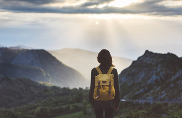 Hipster young girl with bright backpack enjoying sunset on peak of foggy mountain. Tourist traveler on background valley landscape view mockup. Hiker looking sunlight flare in trip in northern spain