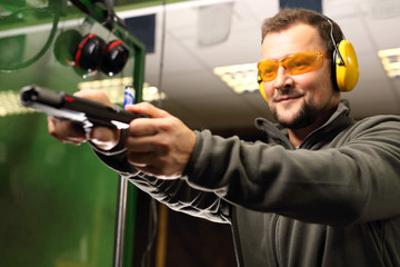 Strzelnica. Mężczyzna na strzelnicy przeładowuje pistolet