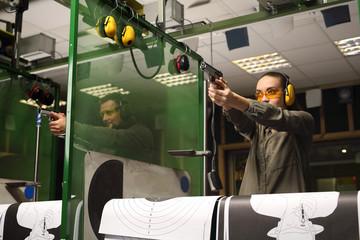 Nauka strzelania z pistoletu. Kobieta celuje do tarczy z pistoletu