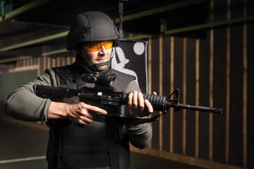 Ćwiczenia wojskowe na strzelnicy. Mężczyzna  w kamizelce kuloodpornej strzela na strzelnicy z karabinu