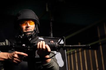 Policjant na strzelnicy strzela z karabinu. Mężczyzna  w kamizelce kuloodpornej strzela na strzelnicy z karabinu