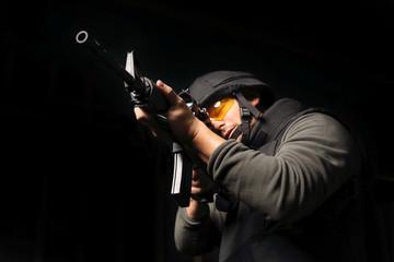 Mężczyzna z karabinem  ubrany w kamizelkę kuloodporna i hełm