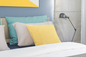 Yellow and green pillow on bed with black foldable lamp on bedside table in modern interior bedroom