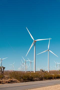 Wind turbines on a windfarm in California USA.   Road and wind turbines on a field.