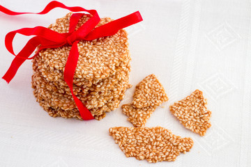 Healthy snack sesame crisps chips with red ribbon on light background