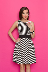 Elegant Woman In Striped Dress Against Pink Background