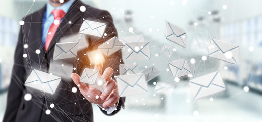 Businessman touching 3D rendering flying email icon with his fin