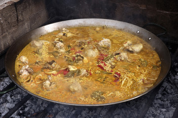 Close up of a paella, cooked on a grill