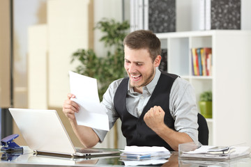 Excited businessman reading a letter at office