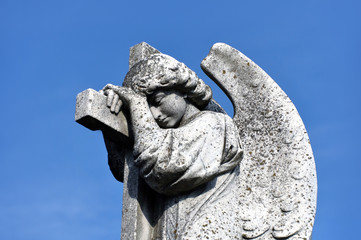 Ancient sculpture of a crying angel of concrete against the blue sky.