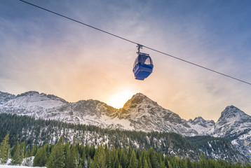 Cable car route over the Alps mountains - Cable car route going over the Austrian alps mountains with their fir forests, while the sun sets down behind the peaks. Image taken in Ehrwald, Austria. Wall mural