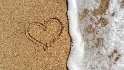 Heart drawing in the sand and sea foam