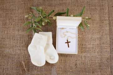 Christening accessories: little white socks, a box with golden cross and olive branch on a sacking background