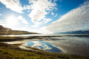 Sunlights and blue sky reflected in the water, Iceland.