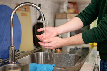 Man washing his dirty hands in the kitchen faucet