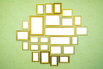 Many empty golden wooden frames with copy space on green wallpapered wall.
