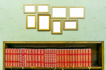Many empty golden wooden frames with copy space on green wallpapered wall. Bookshelf with red books vintage style.
