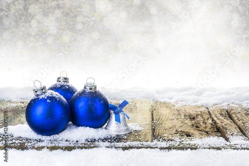 blaue weihnachtskugeln und weihnachtsglocke auf verschneiten holzbrettern vor bokehhintergrund. Black Bedroom Furniture Sets. Home Design Ideas
