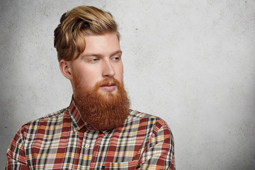 Portrait of young Caucasian brutal man with fuzzy beard wearing red checkered shirt looking away with thoughtful expression. Headshot of handsome hipster model with stylish haircut posing in studio