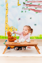 Little girl playing with her teddy bear at tea party using child