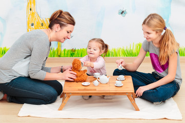 Little girl playing with mom and sister at tea party using child