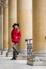 Elegant young woman wearing red coat and black hat