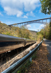 Fototapete - Train runs under the New River Gorge Bridge in West Virginia