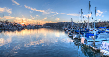 Sunset over sailboats in Dana Point harbor in the fall.