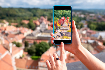 Photographing with smart phone aerial view on the old town of Vilnius city in Lithuania