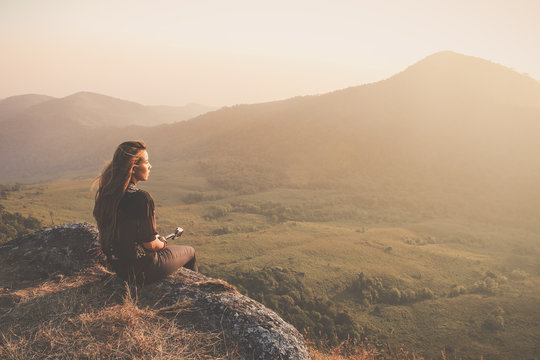 Hipster young girl with backpack enjoying sunset on peak of foggy mountain. Tourist traveler on background view mockup. Hiker looking sunlight in trip in Thailand country. Vintage filtered image.