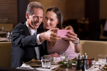 Cheerful couple taking a selfie in the restaurant