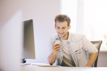 Smiling man talking on mobile phone while using laptop computer at desk in study.