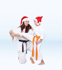 In caps of Santa Claus Mother is training the son kick leg