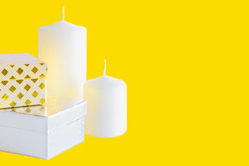 Two gift small boxes and candles on yellow background