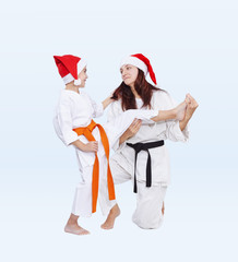 With black and orange belt in caps of Santa Claus sport family are training kick leg