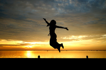silhouette of woman jumping at the sea