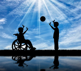 Happy boy in a wheelchair playing with boy in ball